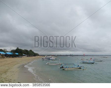 Denpasar, Indonesia - September 27, 2019: Jukung boats sailing on the sea at Sanur Beach.