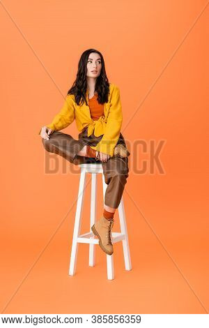 Fashionable Woman In Autumn Outfit Sitting On White Stool And Looking Away On Orange