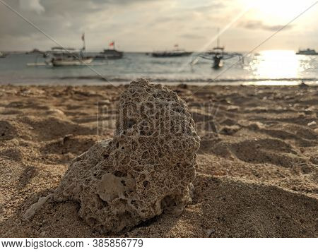 Denpasar, Indonesia - September 27, 2019: A Rock On The Sand With The Background Of Sailing Boats At