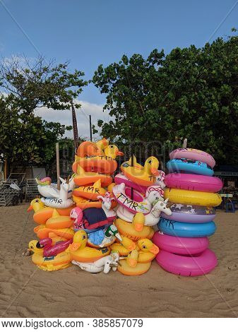 Denpasar, Indonesia - September 27, 2019: Stacks Of Colorful Swim Rings On The Sand In Sanur Beach A