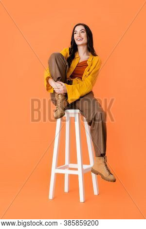 Pleased Woman In Autumn Outfit Sitting On White Stool On Orange