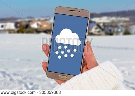 Winter Snow Weather Forecast Concept With Hand Holding Mobile Phone With Snow Icon In Front Of White