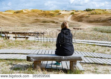 Blonde Hair Girl On The Wooden Bench And Path Looking At Nagliai Nature Reserve In Neringa, Lithuani