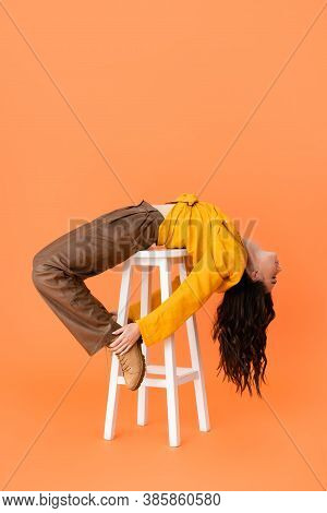 Trendy Woman In Autumn Outfit Lying On White Stool And Touching Boots Isolated On Orange