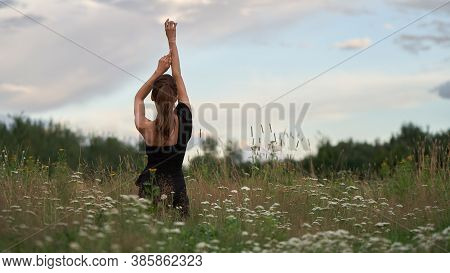 Back View Of A Young Woman Is Relaxing In Nature