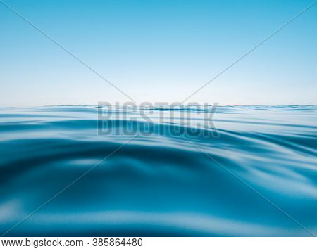 Waterline Surface With Waves And Clear Blue Sky. Clear Horizon.