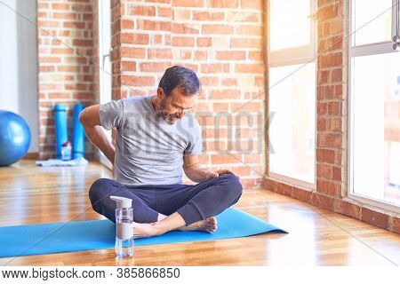 Middle age handsome sportman sitting on mat doing stretching yoga exercise at gym Suffering of backache, touching back with hand, muscular pain