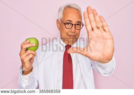 Middle age senior grey-haired nutritionist man holding healthy green apple over pink background with open hand doing stop sign with serious and confident expression, defense gesture