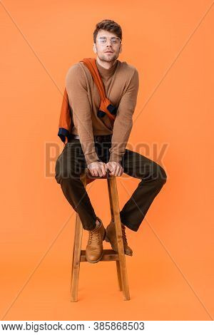 Trendy Man In Autumn Outfit And Glasses Sitting On Wooden Stool On Orange