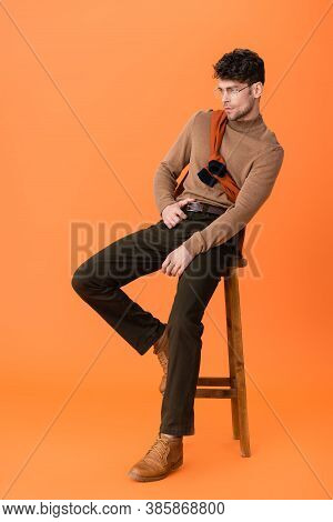 Stylish Man In Autumn Outfit And Glasses Sitting On Wooden Stool On Orange