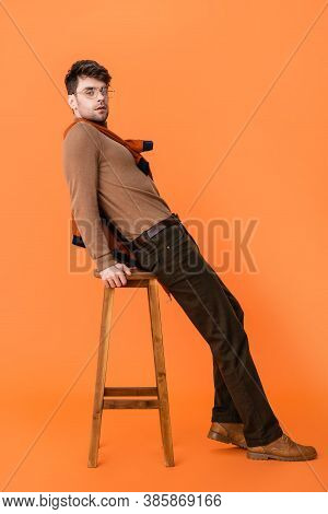 Stylish Man In Autumn Outfit And Glasses Leaning On Wooden Stool On Orange
