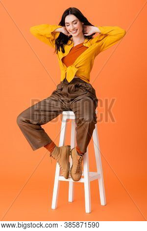 Full Length Of Trendy Woman In Autumn Outfit And Boots Sitting On White Stool And Looking Down On Or
