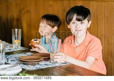 Two Children Having Lunch. Smiling Happy Boy With Down Syndrome With His Brother Sitting Together At