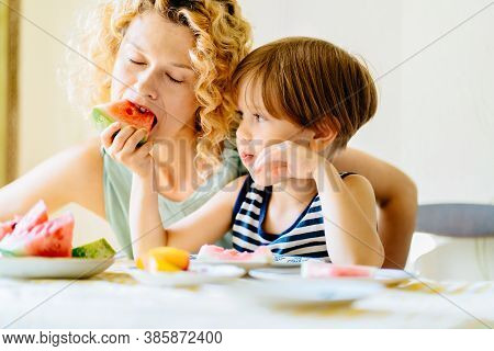 Blond Curly Sweden Woman Play With Her Child. Family Sit Together At Kitchen Table. Mother Eat Slice