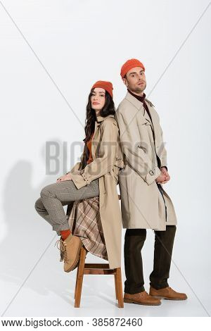 Full Length Of Stylish Woman In Trench Coat Sitting On Stool And Looking At Camera Near Trendy Man O