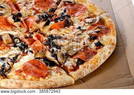 Whole Pizza Cut Into Pieces With Black Olives, Mushrooms, Salami, Cheese And  Tomato Sauce On Cardbo