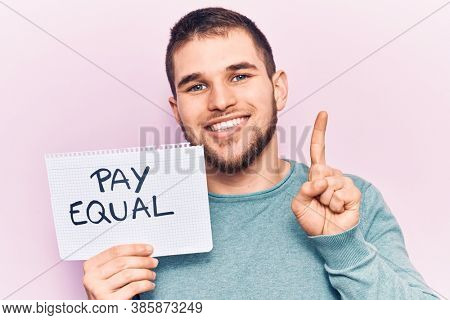 Young handsome man holding pay equal paper smiling with an idea or question pointing finger with happy face, number one