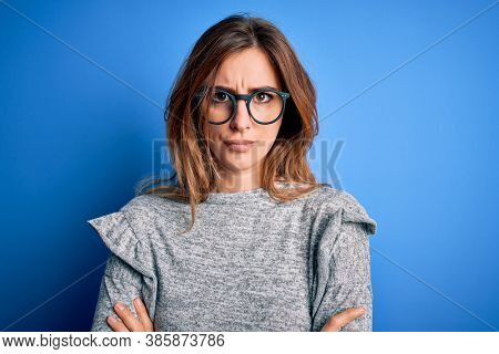Young beautiful brunette woman wearing casual sweater and glasses over blue background skeptic and nervous, disapproving expression on face with crossed arms. Negative person.