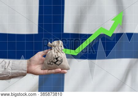 The Concept Of Economic Growth In Republic Of Finland. Hand Holds A Bag With Money And An Upward Arr