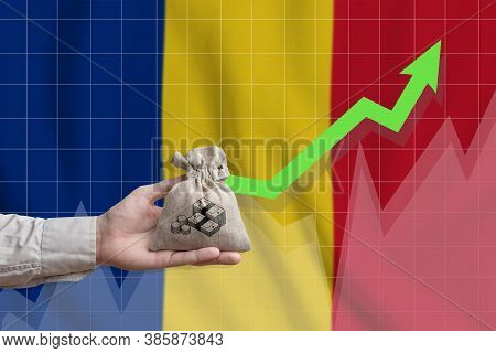 The Concept Of Economic Growth In Romania. Hand Holds A Bag With Money And An Upward Arrow.