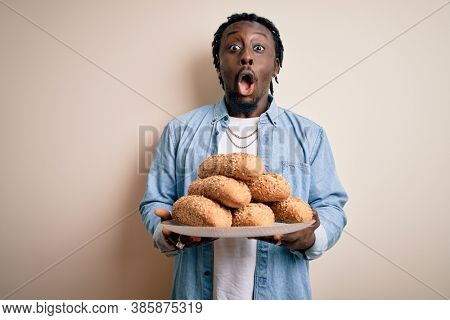 Young african american man holding tray with healthy wholemeal bread over white background scared in shock with a surprise face, afraid and excited with fear expression
