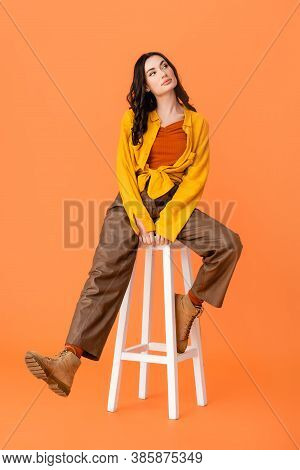 Full Length Of Young Woman In Autumn Outfit And Boots Sitting On White Stool On Orange