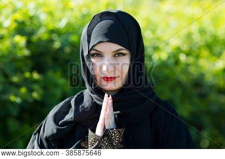 Arab Woman In Black Clothes Prays To God. Arab Woman In Black Clothes Prays To God Against A Backgro