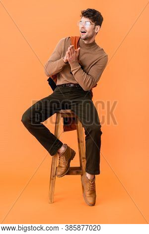 Stylish Man In Autumn Outfit And Glasses Sitting With Praying Hands On Wooden Stool On Orange