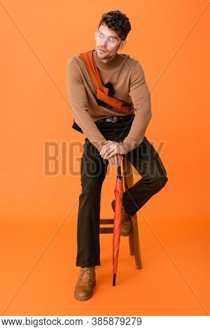 Stylish Man In Autumn Outfit And Glasses Holding Umbrella While Sitting On Wooden Stool On Orange
