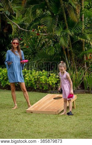 Happy Family Playing Cornhole Game By The Sea On Sunny Summer Day. Parents And Children Playing Bean