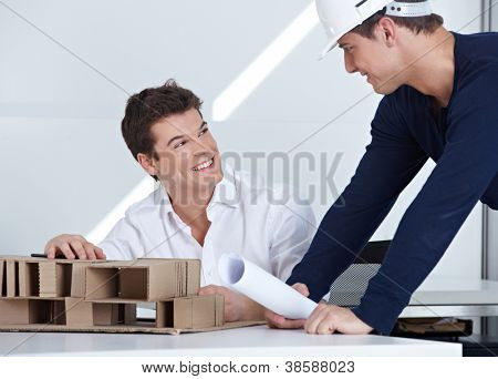 Architect with hardhat and blueprint talking to his employees in the office
