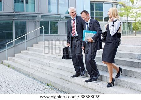 Three business people descending a stairway and talking