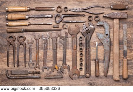 Collection of vintage tools such as wrenches, hammer, chisels and other on old wooden background, top view