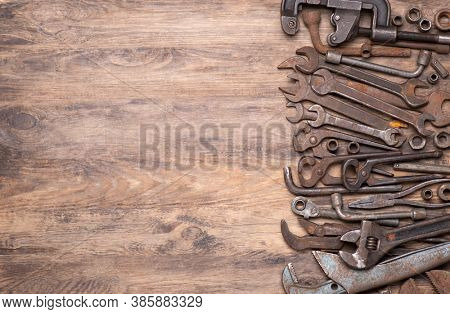 Collection of vintage tools such as wrenches, spanners and other on old wooden background, top view with copy space