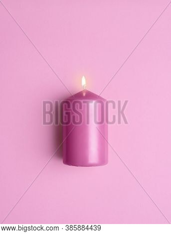 Pink Candle Burning Isolated On A Pink Seamless Background. Flat Lay With A Single Lit Candle. An Ar