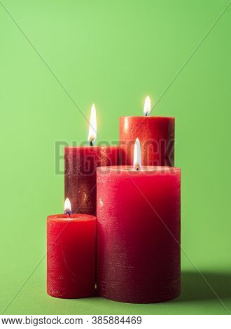 Group Of Lit Candles Isolated On A Green Colored Background. Wax Candles Red-colored. Red Candles On