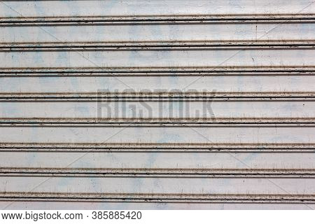 Background Of White Horizontal Metal Strips With Peeling Paint. Roller Blinds And Garage Gates. Clos