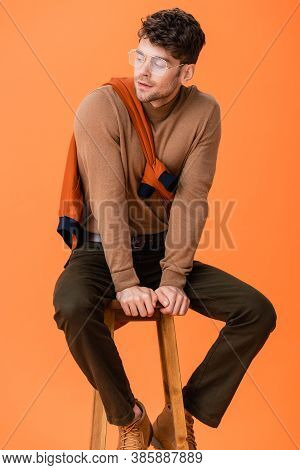 Stylish Man In Autumn Outfit And Glasses Sitting On Wooden Stool And Looking Away Isolated On Orange