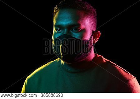 health, safety and pandemic concept - young african american man wearing reusable protective mask over black background