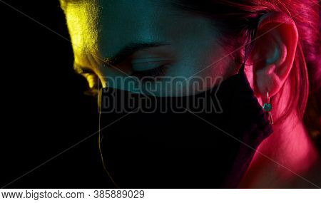 health, safety and pandemic concept - close up of sad young woman wearing reusable protective mask over black background