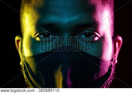 health, safety and pandemic concept - close up of young african american man wearing reusable protective mask over black background