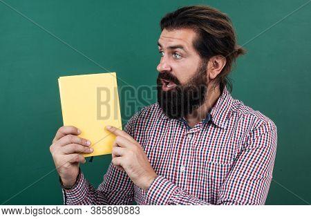 Look At That. Informal Education. Surprised Mature Teacher Reading Book. Brutal Bearded Man Work In