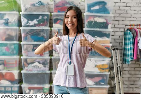Young Woman Smiling At Camera, Showing Thumbs Up, Posing In Front Of Rack And Boxes Full Of Clothes,