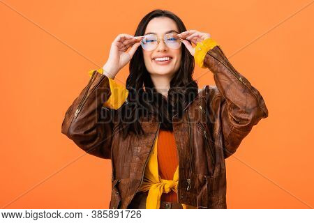 Stylish Woman In Autumn Outfit Touching Glasses Isolated On Orange