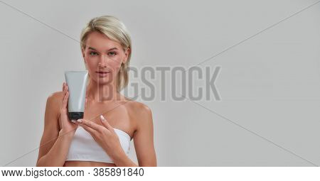 Portrait Of Young Woman With Perfect Fresh Skin Looking At Camera, Holding Cosmetic Skincare, Bodyca