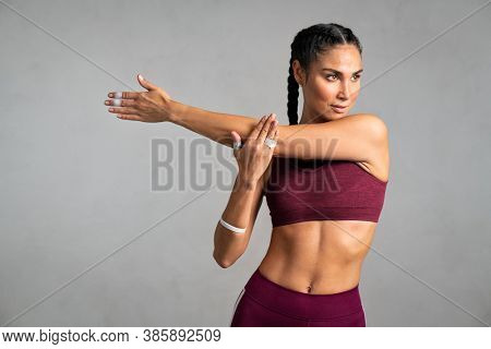 Portrait of fit middle aged woman doing arm stretching isolated on grey background. Determined latin woman warming up before training on gray background with copy space. Woman doing fitness exercise.