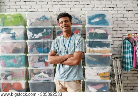 Cheerful Guy Smiling At Camera, Posing With Arms Crossed In Front Of Rack And Boxes Full Of Clothes,