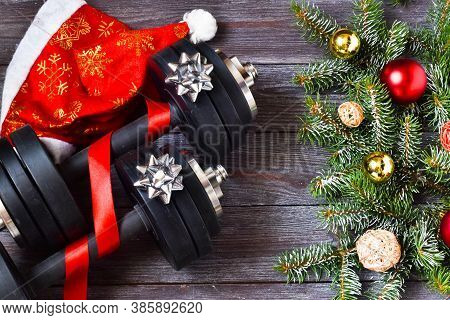 Cristmas Sports. Black Sport Dumbbells, Gifts And Bows On Wooden Background. Merry Christmas And Hap