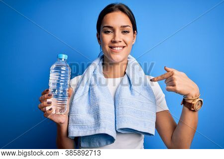 Young beautiful brunette sportswoman wearing towel drinking bottle of water to refreshment with surprise face pointing finger to himself