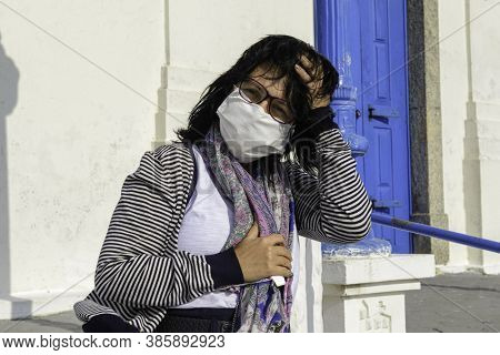 Mature Woman Protects Herself From The Wind In Front Of A Church Wearing Mascara